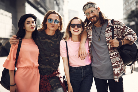 Portrait of positive men and happy females embracing while situating outdoor in modern city. They wearing modern clothes and looking at camera. Satisfied comrades at street concept Фото со стока