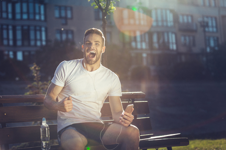Yes. Waist up portrait of thrilled attractive male sitting outside and screaming in joy. He is holding mobile while opening mouth in delight. Copy space in right side