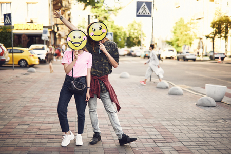 Full length portrait of cheerful man and smiling girl with emoji faces standing at street. Glad guy gesticulating hand Imagens