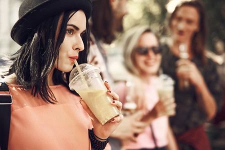 Side view pensive girl drinking delicious cocktail while having fun with friends Stock Photo