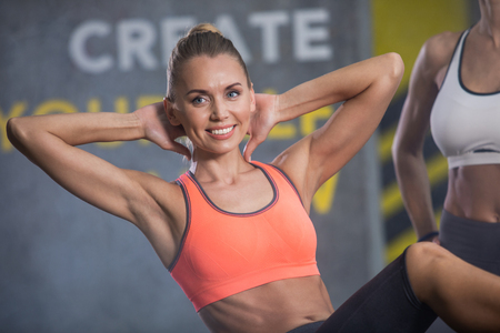 Portrait of smiling woman doing abdominal crunches in gym. She is bending arms behind head during effort while other athletic female is staying near her. Training with pleasure concept