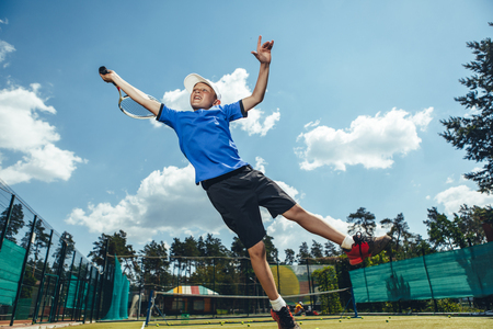 Full length portrait of cheerful boy gesticulating hand with racket while trying to hit ball during tennis game