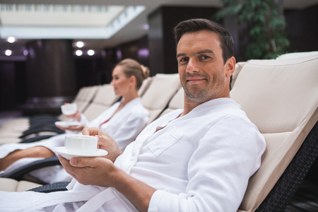 Focus on waist up portrait of joyful male sitting on deckchair with cup of favorite hot drink. He is enjoying relaxation time. Young woman in bathrobe is on background Stock Photo