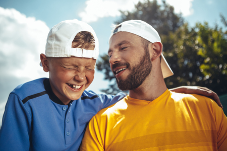 Portrait of laughing boy telling with cheerful bearded man while embracing him. They resting outdoor under blue sky and green tree