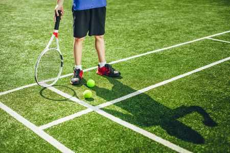 Close up boy legs standing on court. His shadow locating there. He moving hands while holding sport equipment