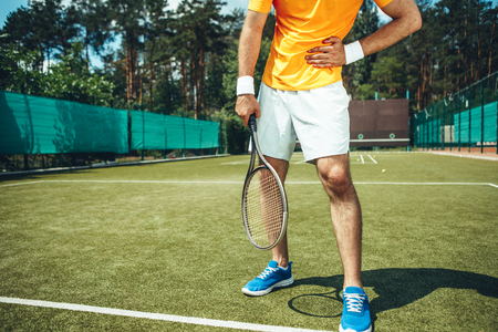 Man having pain in rib while keeping it with arm during tennis game on contemporary court with green grass