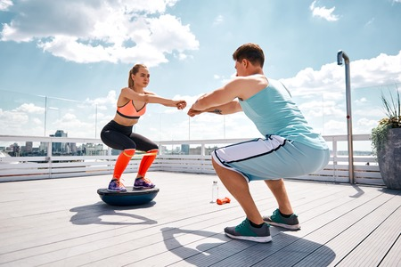 Strong man is doing sit-ups while girlfriend is squatting on fitness half ball and using resistance band on thighs. They are having joint work out on sunny terrace in city center under blue sky. Training with partner for pleasure concept