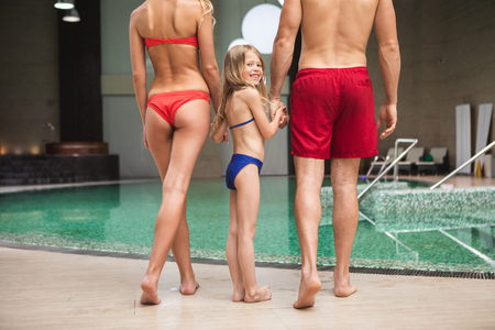Full length of smiling kid holding parents hands by pool. Man and woman are standing with turned backs in swimsuits ready to plunge into water