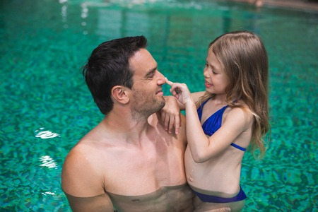 My daddy. Profile of happy father holding daughter in pool. Small girl is looking at man and touching his nose with smile. They are delighted to spend time side by side
