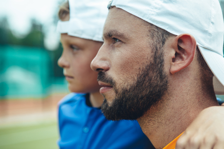 Side view orderly little boy embracing serene young unshaven sportsman outdoor