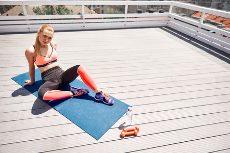 Top view of calm fit lady sitting and relaxing on wide wooden terrace above city. She is training on mat with dumbbells and now having break. Copy space in right side