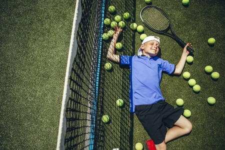 Top view portrait of smiling tired child lying on green grass near net around balls for playing tennis