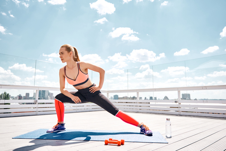 Slender girl is doing side lunges on terrace of house in city center. She is warming-up before training with dumbbells. Work out with weights for female concept