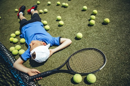 Top view full length calm boy relaxing on court while keeping racket
