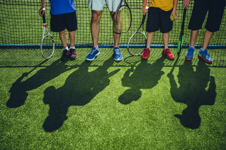 Close up male athlete feet situating near children. They keeping sport equipment. Their silhouettes situating on court