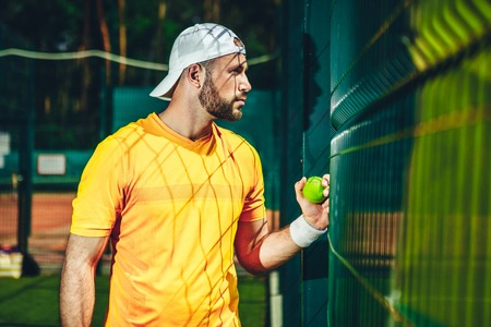 Side view concentrated bearded man looking through fence while holding boll for play tennis. He wearing cap on head Stock fotó