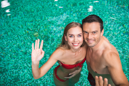 Waist up portrait of happy man and woman standing in water in swimsuits. They are bonding to each other and waving hands with joy Stock Photo