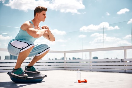 Athlete is doing sit-ups and balancing on BOSU ball. He is exercising on sunny terrace in skies above city. Copy space in right side