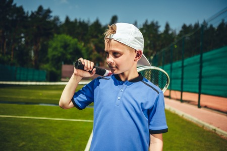 Pensive child holding sport tool in hand during game on contemporary court Stock Photo