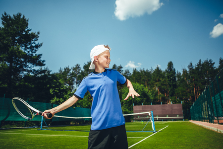 Side view cheerful boy gesticulating hands with racket while playing tennis on court outdoor. He standing opposite net