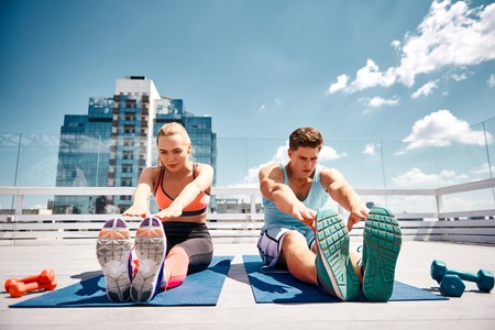 Sporty couple are stretching together on top of high urban building. They are sitting on mats and bending to straight less. They are finishing strength training with dumbbells