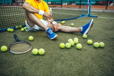 Exhausted man holding beverage while locating on field after good training. Sport equipment situating near him Stock Photo