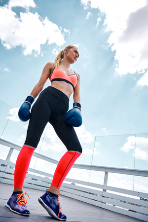 Low angle of slender woman having combat workout. She is standing in sportswear and gloves and looking forward with confidence. Girl is training on wide open balcony under sky Фото со стока