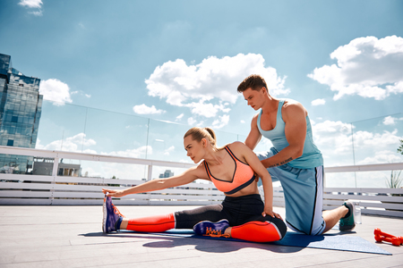 Male coach is helping slim girl with stretching by pushing her back. Athletic lady is sitting and bending body to leg. They are training on sunny terrace of urban building