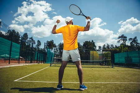 Full length male holding racket while gesticulating arms. He standing on modern court for tennis game during sunny day