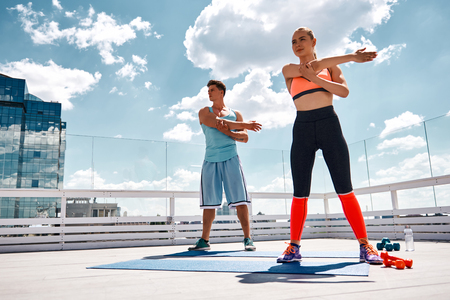 Athletic man and woman are standing and stretching one arm while holding it with another. They are getting ready for training with dumbbells. Male and female are exercising under blue sky on roof of urban building