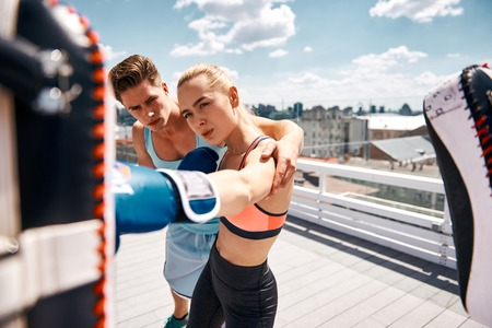 Woman is working on cross kick while her partner is defending with pads. Male instructor is assisting her by hugging and controlling correct punch. They are training together on terrace in city center