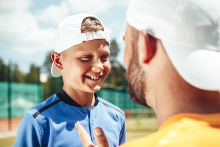 Beaming child expressing gladness while speaking with coach on field. He gesticulating hand