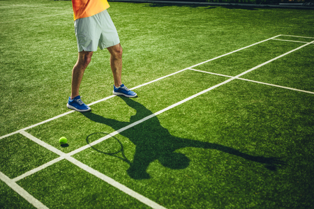 Close up man legs with silhouette situating on green court. He holding racquet in arm while gesticulating it Banco de Imagens