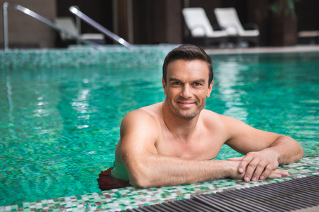 Waist up portrait of smiling male swimming in pool. He is leaning with hands against poolside and looking at camera with satisfaction