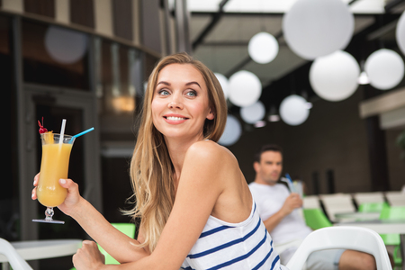 Focus on waist up portrait of smiling female sitting at table and holding glass of cold cocktail. She is looking sideways with delight. Young man is on background Stock Photo