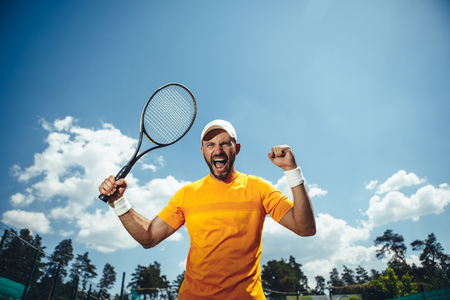 Portrait of cheerful unshaven man gesticulating arm with racket while playing tennis on field outdoor. He shouting and looking at camera Imagens