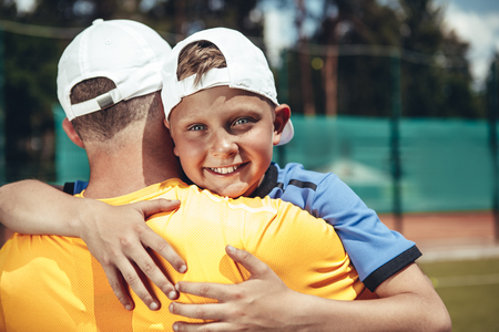 I love you. Outgoing little child hugging dad while situating on field for tennis game. Happy family concept Imagens
