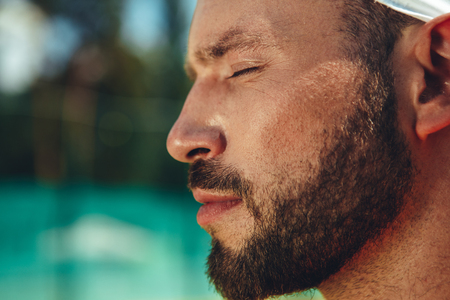 Close up face of serious unshaven man with closing eyes expressing tranquility. Copy space