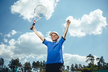 Low angle portrait of beaming kid with racket in arm expressing happiness under clear sky. He playing tennis Banque d'images