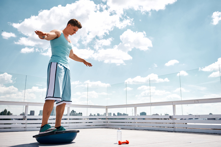 Ripped man is standing on half-ball and lifting arms for finding equilibrium. He is having training with half-ball and dumbbells on top of high urban building in lovely warm weather. Copy space in right side