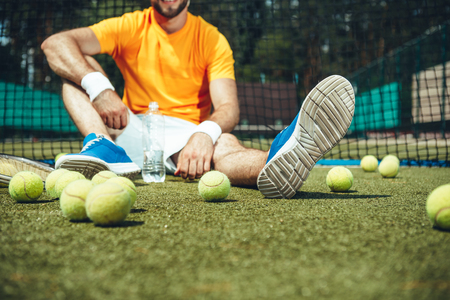 Happy man tasting appetizing beverage while relaxing after tennis. Sport equipment situating near him