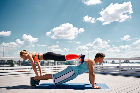Ripped guy and fit lady are training together on sunny roof of urban building. Man is straining while staying in plank as woman is repeating his position while being on him. He is putting feet on male back and balancing by holding his feet with hands Reklamní fotografie