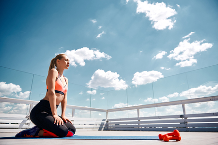 Low angle of tranquil woman training with dumbbells on open balcony under sky. She is sitting and resting after efforts while looking ahead. Copy space in right side