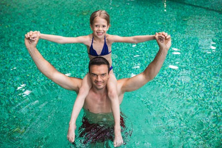 Waist up portrait of male holding child sitting on his shoulders. Small girl is raising hands and looking at camera with joy and smile. They are happy to play and swim together