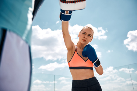 Low angle of sporty lady boxing under blue sky. She is throwing punches at coach pads while using gloves. Exercising for self-defense and health concept
