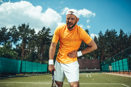 Portrait of shouting sad male athlete feeling ache in stomach during training on field outdoor. He holding racket in hand