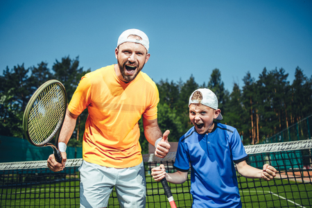 Portrait of shouting positive man and cheerful kid gesticulating hands while looking at camera. They holding rackets and standing on court for playing tennis outdoor
