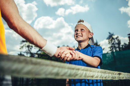 Positive satisfied boy greeting with coach arm while situating outdoor before training Reklamní fotografie