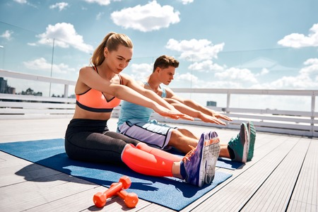 Fit man and woman are straining while stretching on sunny terrace above cityscape. They are sitting and trying to touch feet with arms. They are doing efforts synchronously while motivating each other Stock Photo