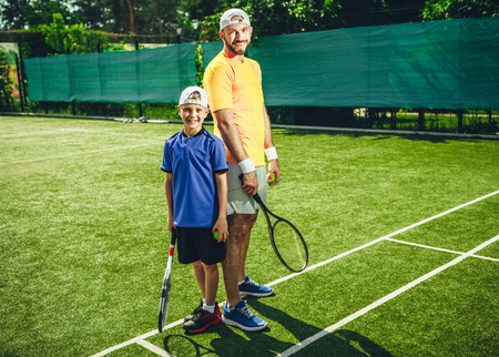 Full length portrait of beaming bearded male athlete and smiling little boy playing tennis while locating on green field. They keeping sport equipment in hands and looking at camera